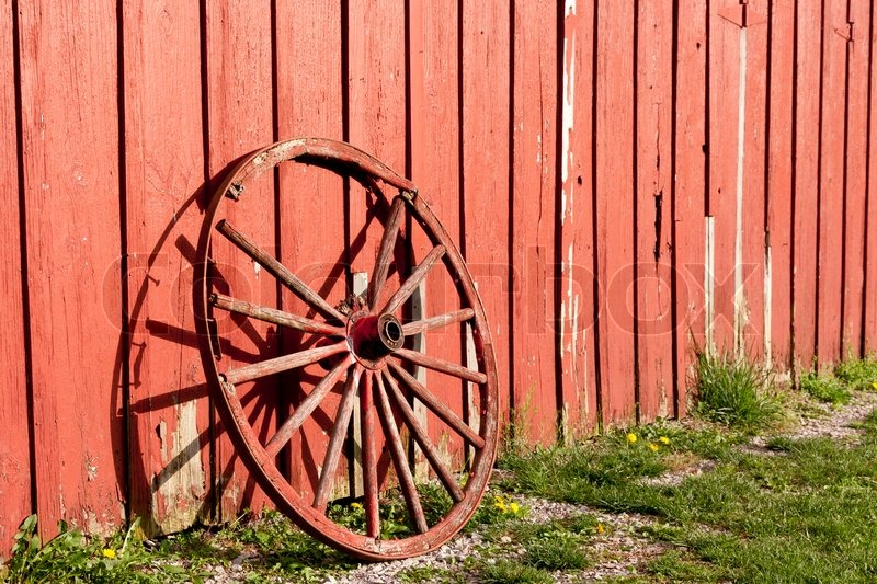 Old Rustic Wagon Wheel Beside A Red Barn Stock Photo
