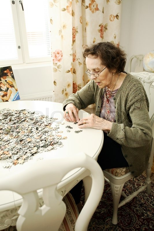 Old Lady Concentrating On A Huge Jigsaw Puzzle At Her