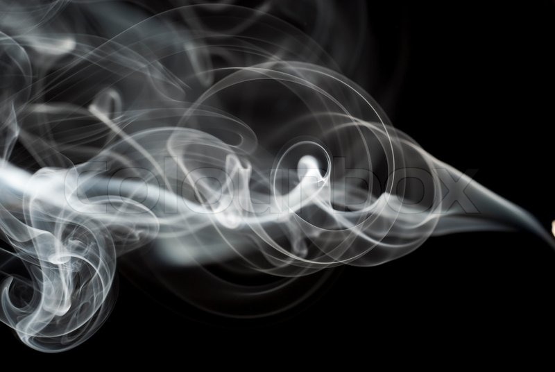 Abstract black smoke swirls over the black background ...