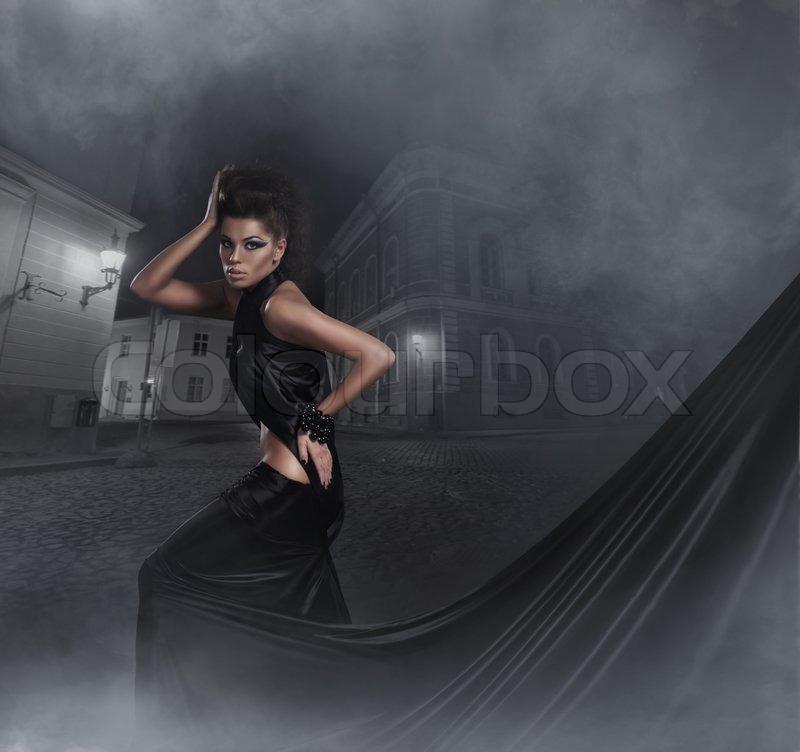 Fashion shoot of young sexy woman in black long dress ...