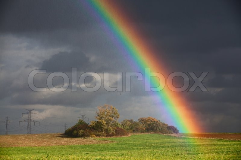 natural rainbow over green field and dark sky stock