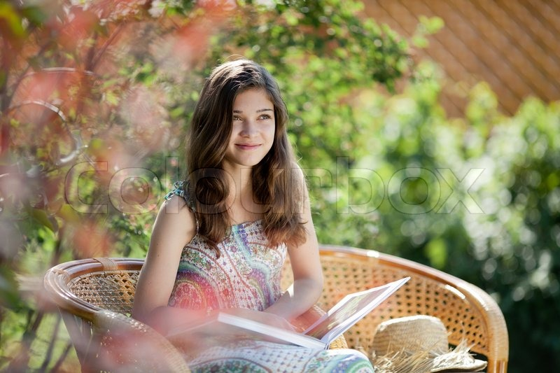 Girl Reading Book Sitting In Wicker Chair Outdoor In