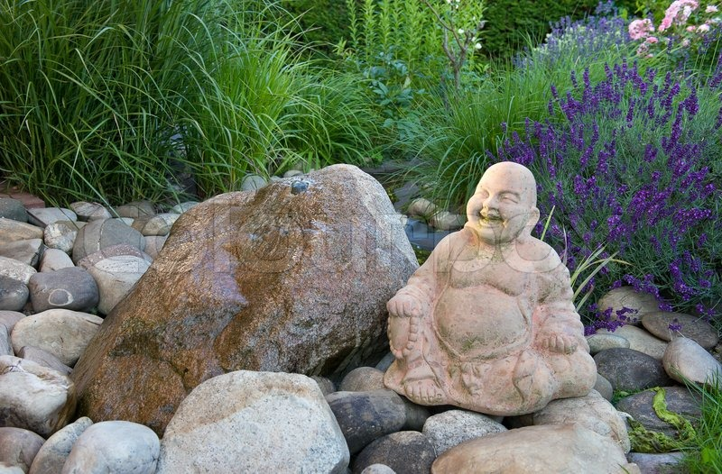 Buddha in green garden with stones and water | Stock Photo | Colourbox