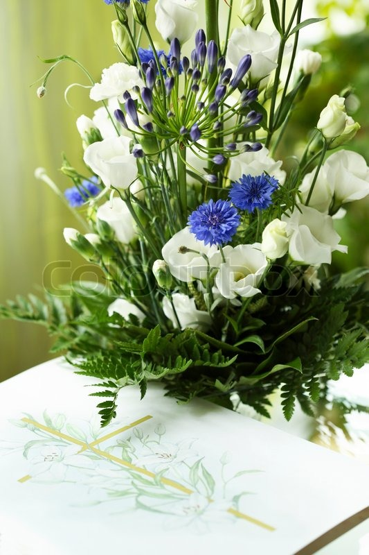 Beautiful condolence bouquet with white and blue flowers over a card ...