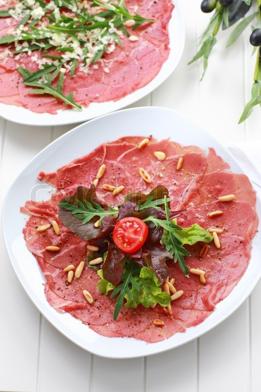 Stock image of 'Carpaccio with salad and pine nut'