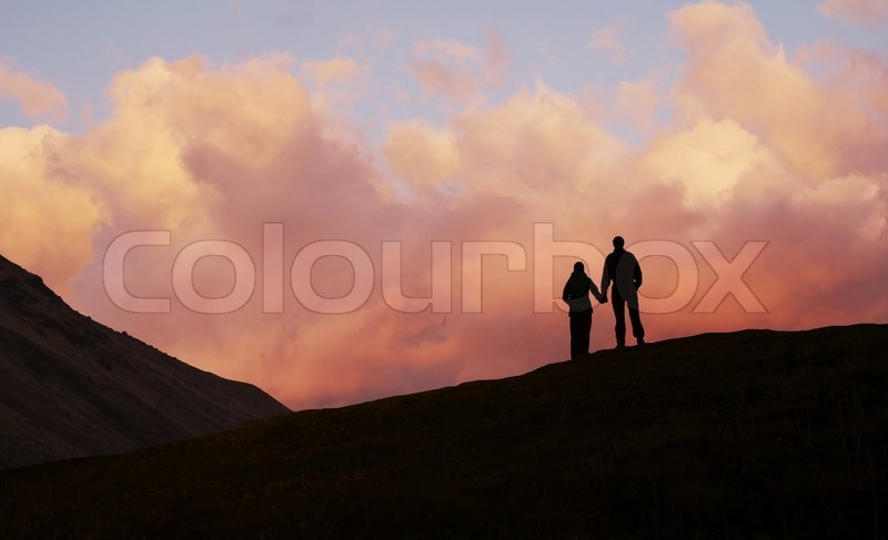 Stock image of 'Boy and girl on sunset background'