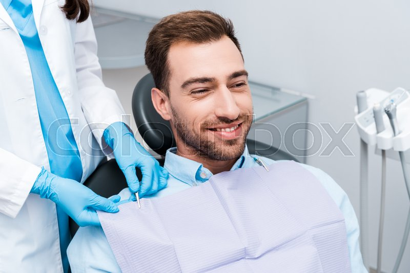 Cropped view of dentist in blue latex ...