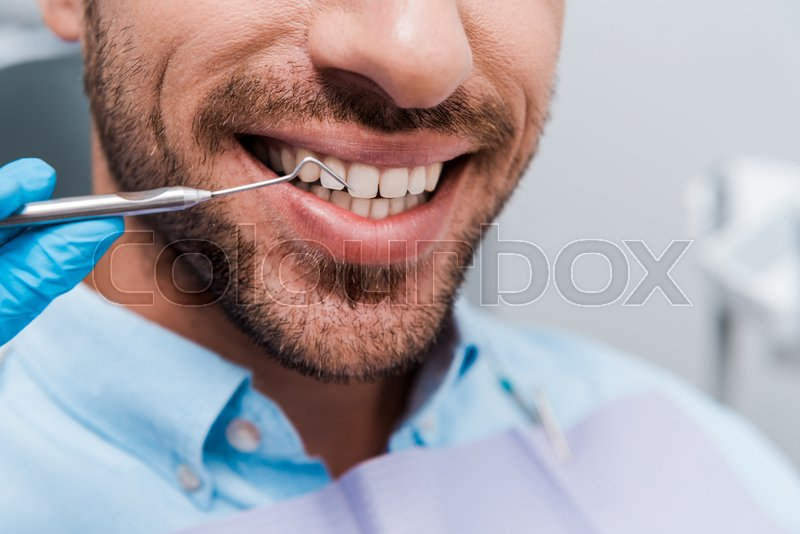 Cropped view of dentist holding dental ...