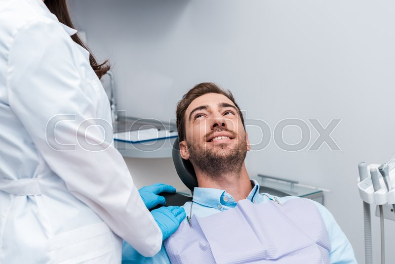 Cropped view of dentist in white coat ...