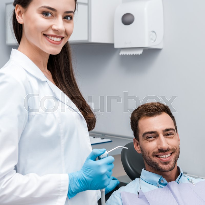 Beautiful and happy dentist holding ...