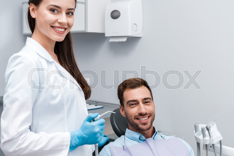 Attractive and happy dentist holding ...