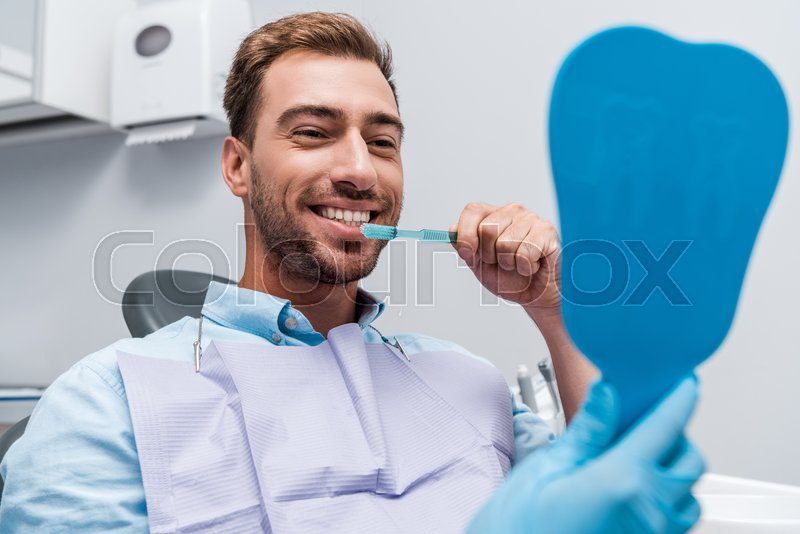 Cropped view of dentist holding mirror ...