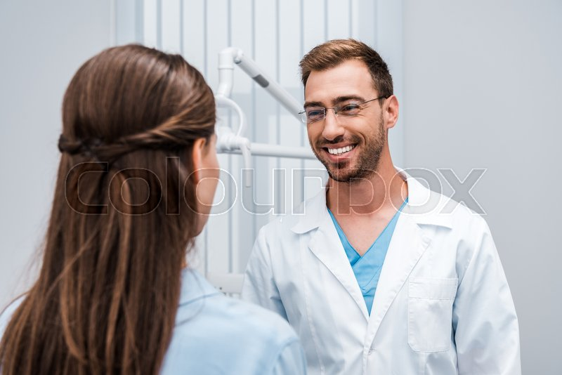 Selective focus of cheerful dentist in ...