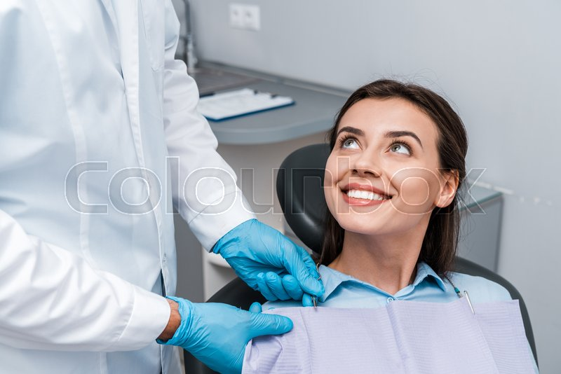 Cropped view of dentist in latex gloves ...