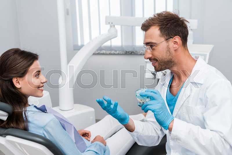 Cheerful dentist in glasses holding ...