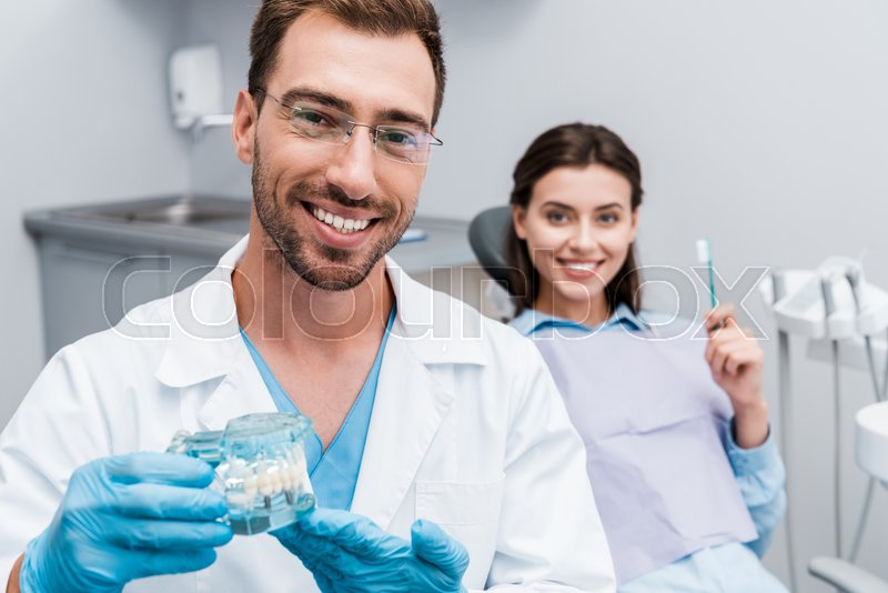 Selective focus of happy dentist in ...