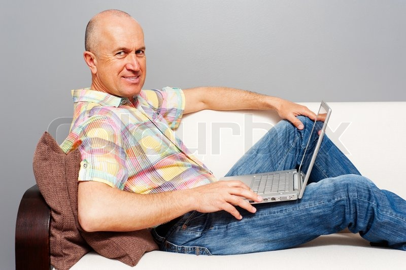 Image of 'elderly man with laptop on sofa'