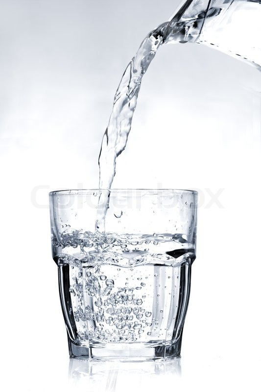 Filling a glass with water on a light blue background, stock photo