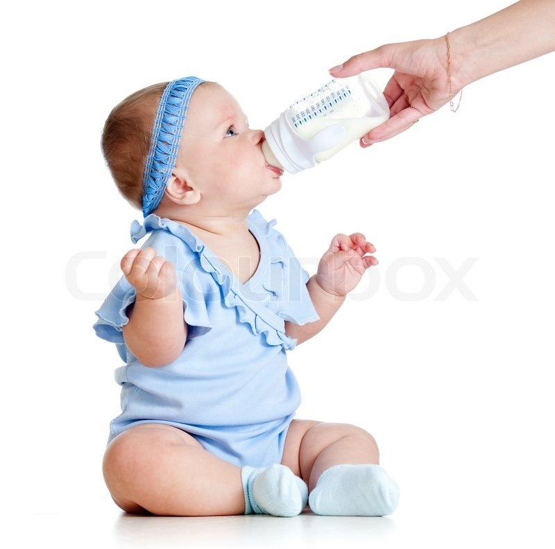 Adorable baby girl drinking from bottle with help of ...