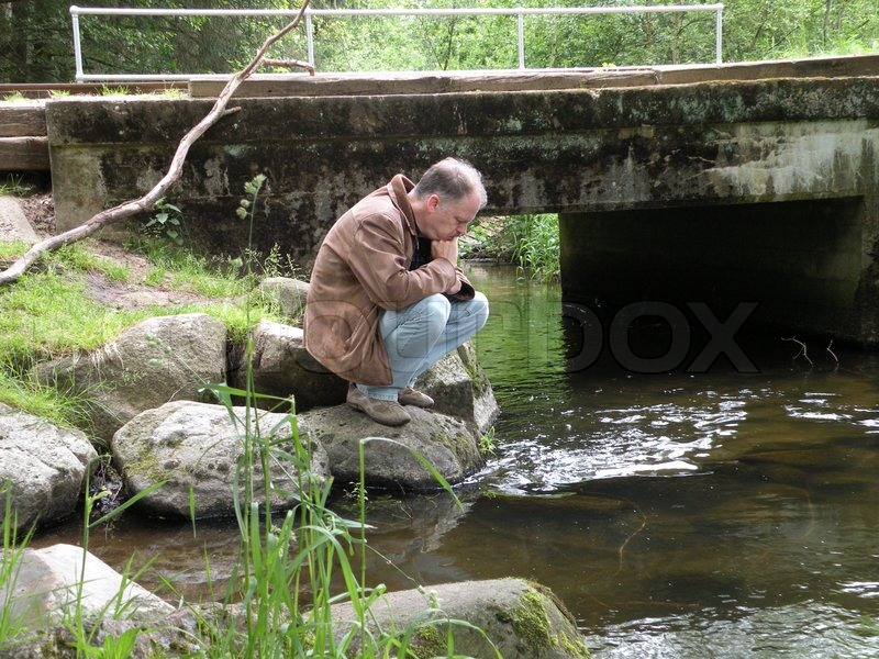 Stock image of 'Man thinking at shore of a river'