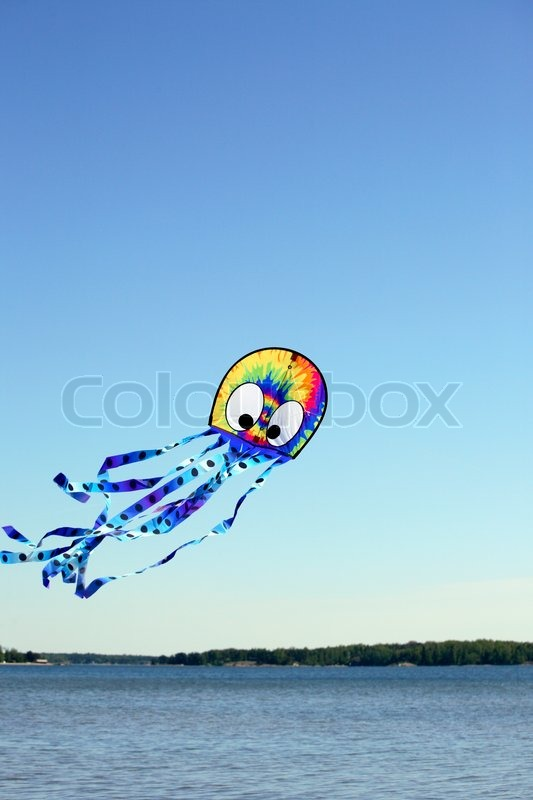 Stock image of 'Colourful wind kite flying over the sea in clear blue sky'