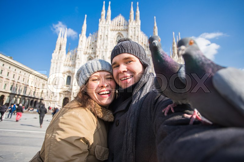 Couple taking self portrait with pigeon ...