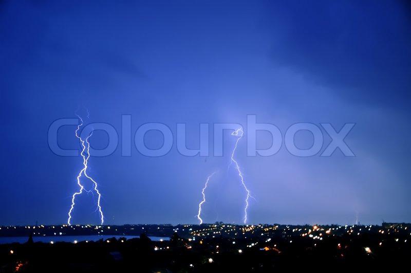 Lightning strike over dark blue sky in night city, stock photo