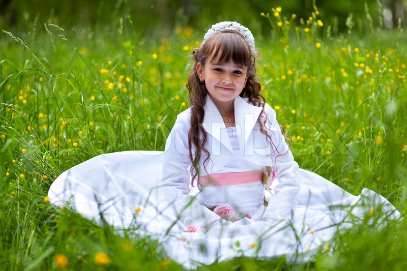 little girl in white dress sitting in stock photo