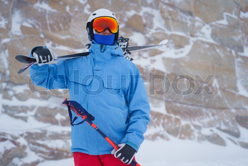 Sports man in helmet with skis in hand ...