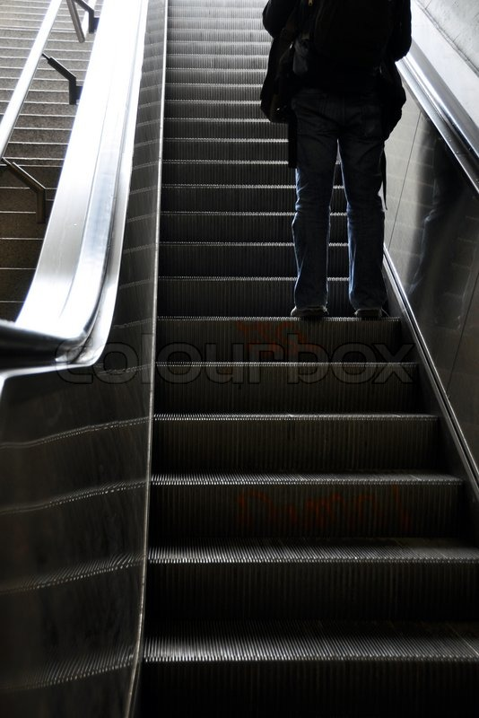 Man moving up with escalator, stock photo