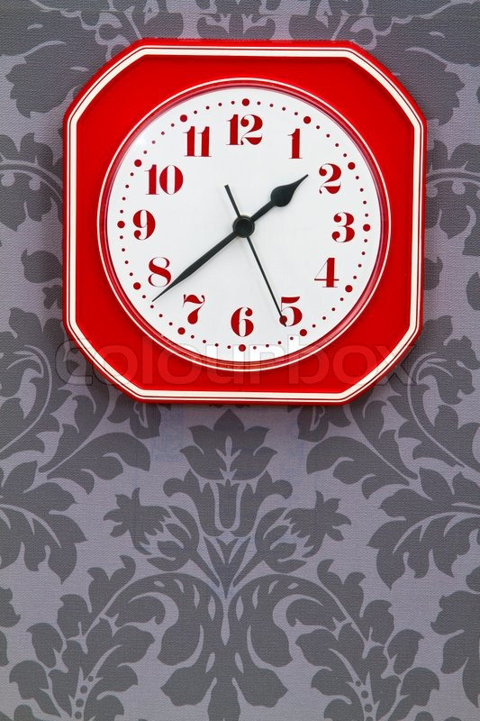 Red Vintage Kitchen Clock On Ornamental Wallpaper Stock