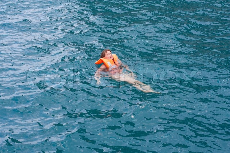 Woman In Orange Life Jacket In Water Of A Sea Stock