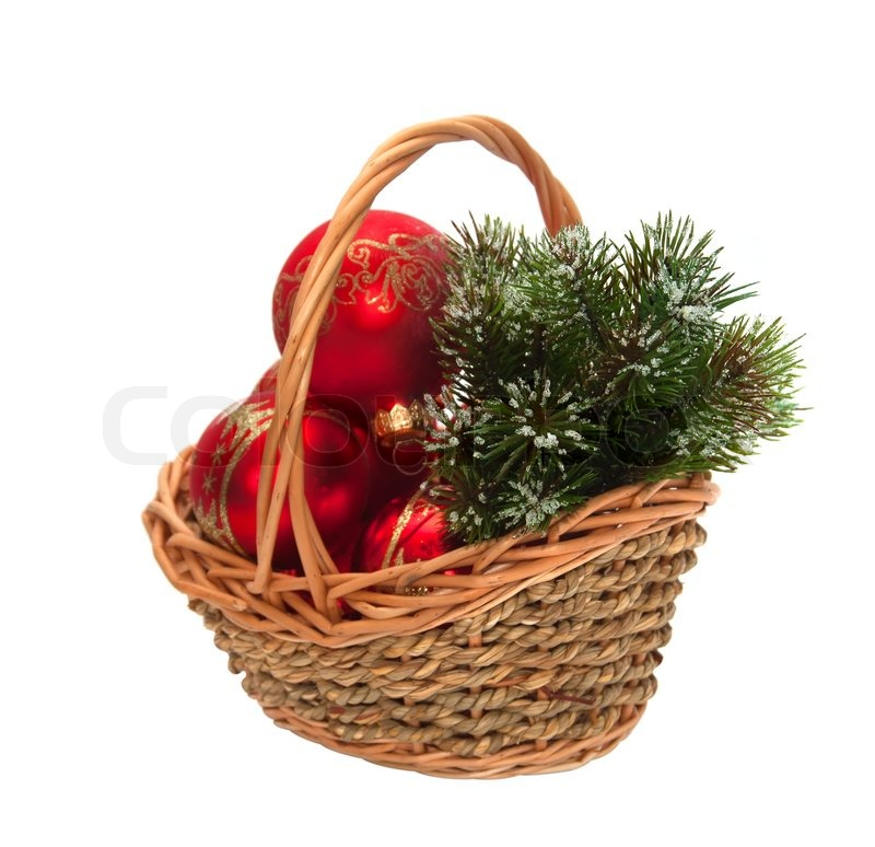Christmas decorations and a branch of pine in a wicker basket ...
