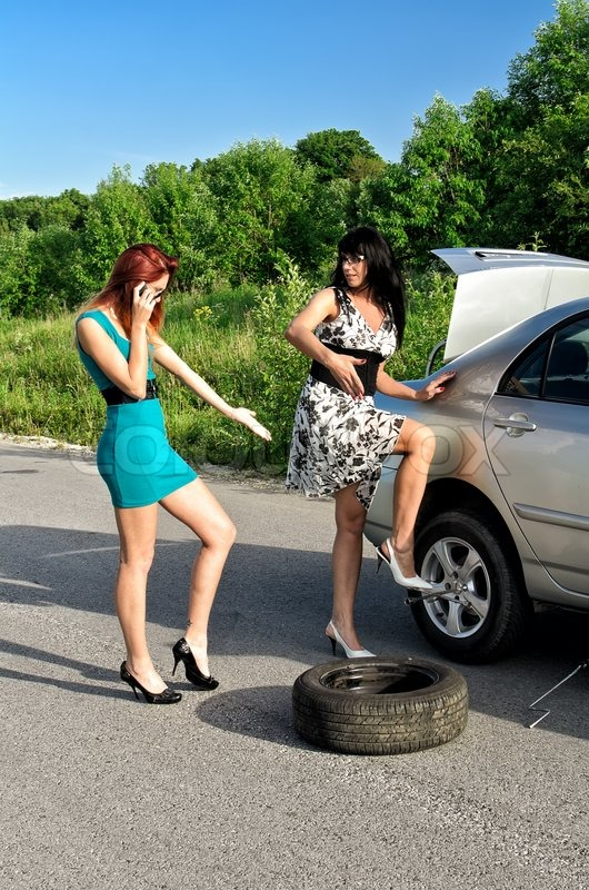 Two Women Are Changing A Tire On A Road  Stock Photo