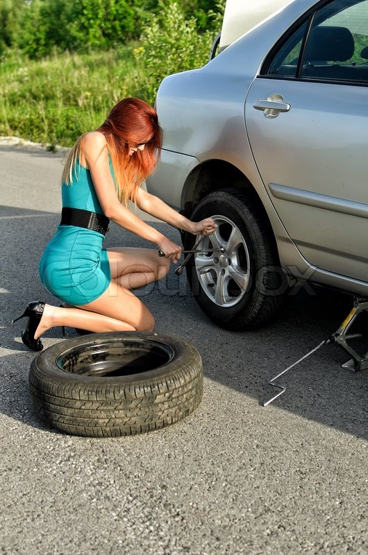 Pretty Girl Is Trying To Change A Tire On A Road Stock
