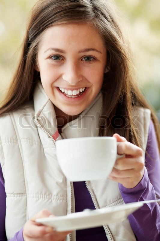 Teenage Girl In Outdoor Caf With Hot Drink Wearing Winter