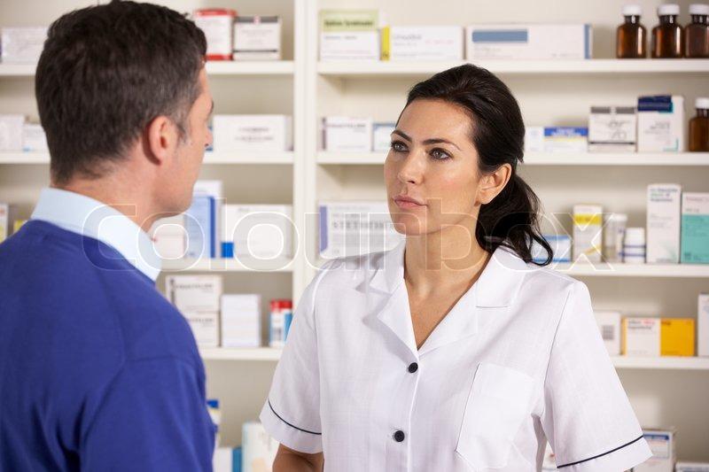 American pharmacist talking to man in pharmacy | Stock Photo | Colourbox