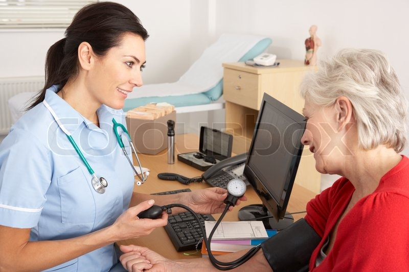 British nurse taking senior woman's blood pressure | Stock ...