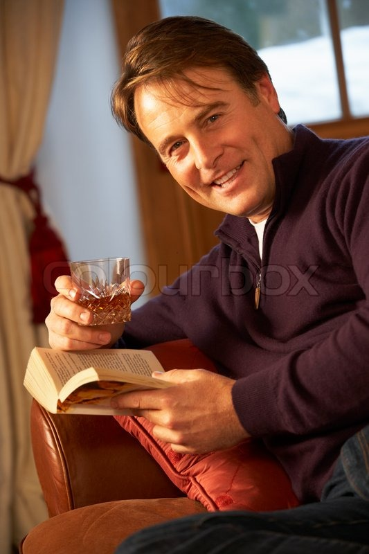 Middle Aged Man Relaxing With Book Sitting On Sofa