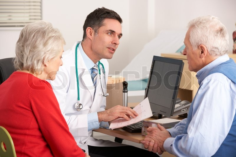 American doctor talking to senior couple in surgery, stock photo