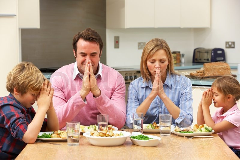Stock image of 'Family saying grace before meal'