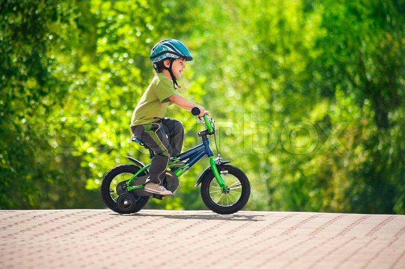 Boy riding bike in a helmet | Stock Photo | Colourbox