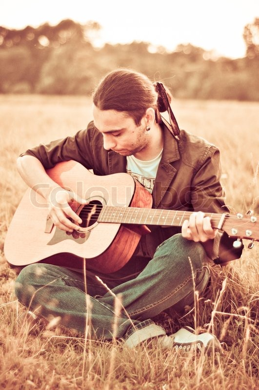 Portrait Of A Handsome Young Man Playing Guitar Outdoors