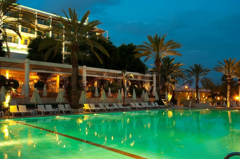 Night Swimming Pool Against The Backdrop Of Palm Trees And