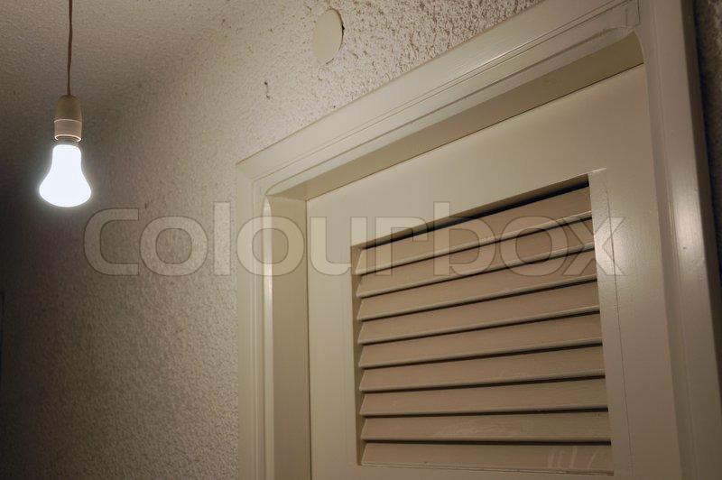 Light bulb and door in dark basement Stock Photo Colourbox