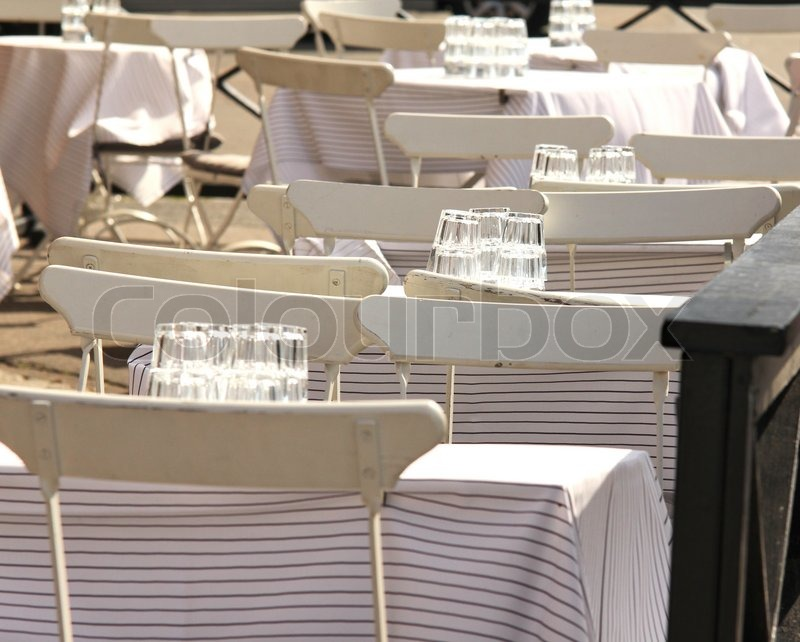 White chairs and tables, outdoors at a restaurant, stock photo