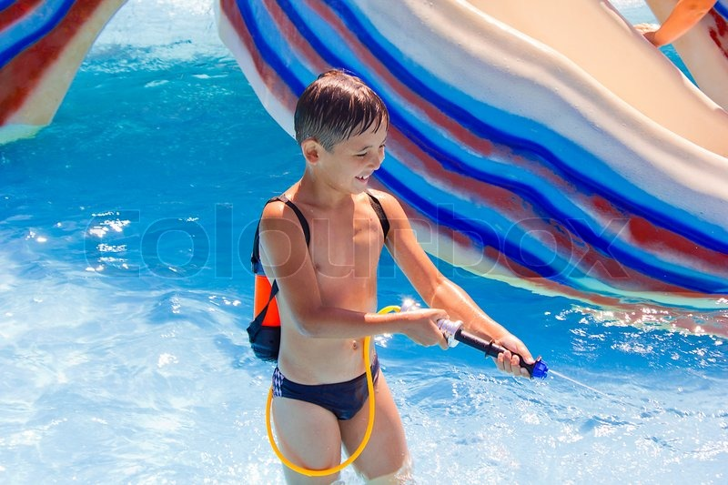 A little boy playing in the pool with a water pistol ...