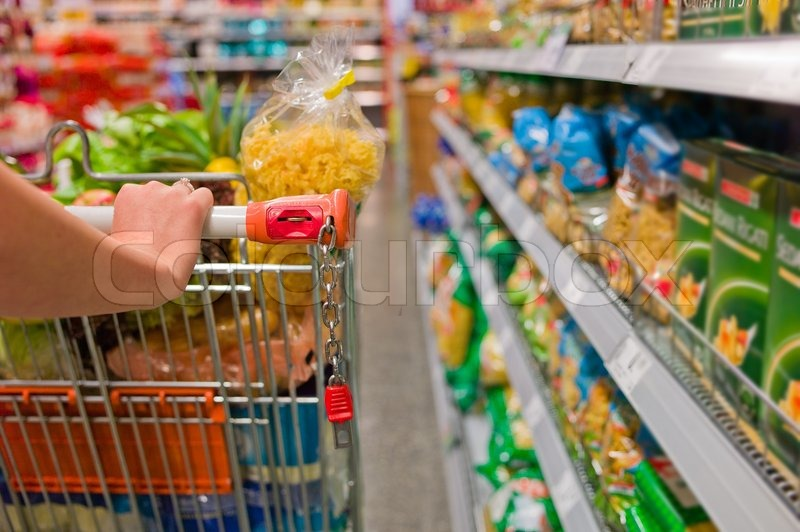 Woman with shopping cart in the supermarket, stock photo
