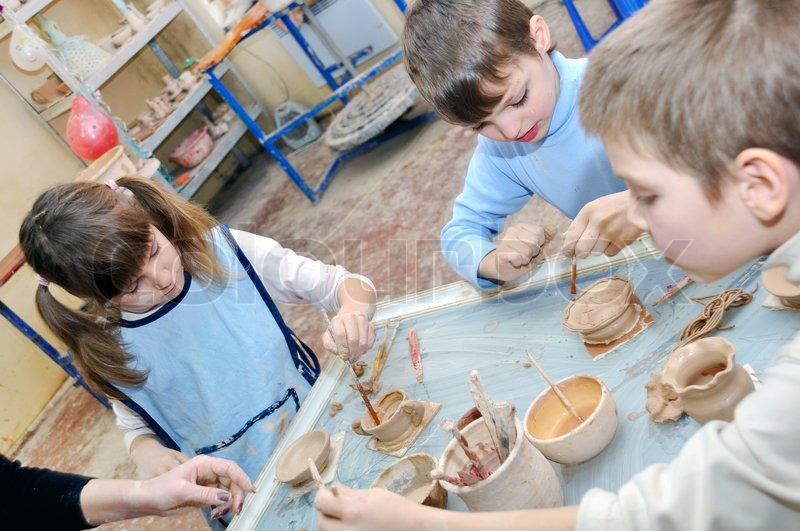 group of children shaping clay in pottery studio stock