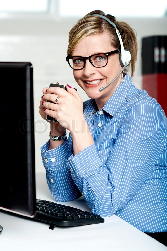Help desk executive drinking coffee at work, stock photo